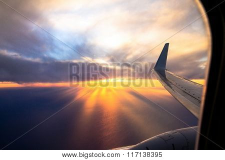 Wing Aircraft At Sunset. Looking Out Through Airplane Window