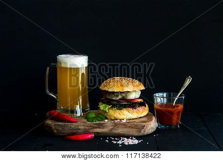 Fresh homemade burger on wooden serving board with spicy tomato sauce, sea salt, herbs and mug of li