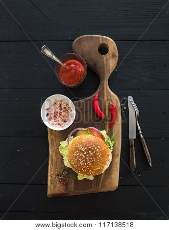 Fresh homemade burger on dark serving board with spicy tomato sauce, sea salt over black wooden back