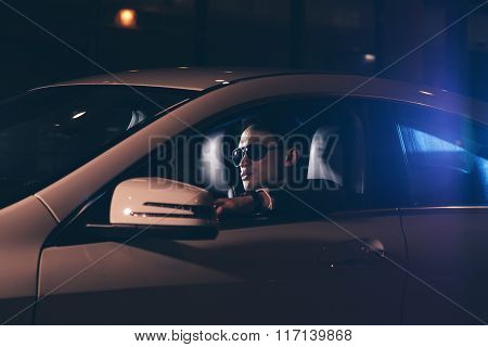 Side View Of Asian Man With Sunglasses In Car At Night.