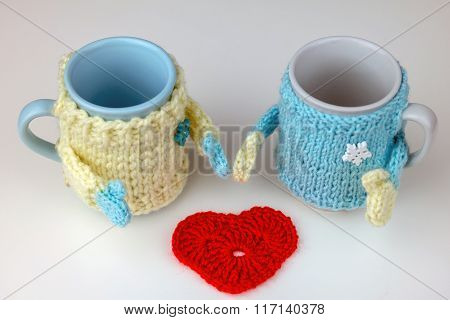 Two cups in sweater and knitted heart.