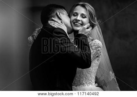 Happy Sensual Handsome Groom And Blonde Beautiful Bride In White Dress Kissing  Close-up B&w