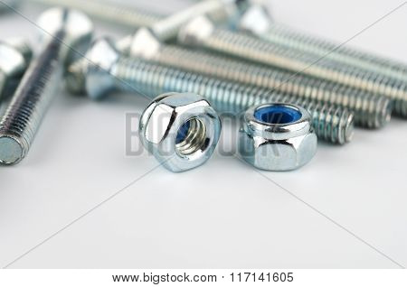 Two Metall Nuts On Background Of Metallic Bolts