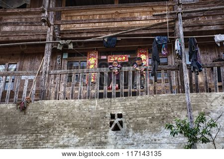 Rural Asian Children Stand On Terrace Of Chinese Wooden Farmhouse.