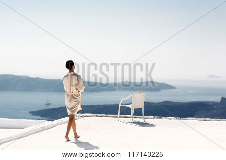 Beautiful Sexy Brunette Bride In Robe Walking On Hotel Roof With Sea And Mountains In Background