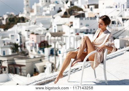 Sexy Brunette Bride With Long Legs Sitting On The Roof With Town Background