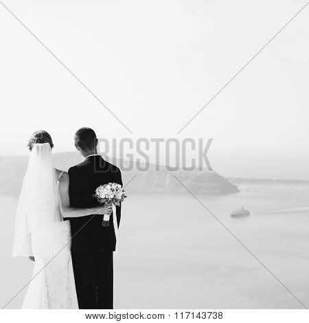 Romantic Couple Hugging On Terrace With Sea, Islands And Mountains In Background B&w