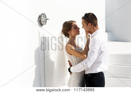 Handsome Groom And Beautiful Sensual Bride Kissing Near White Wall In Santorini