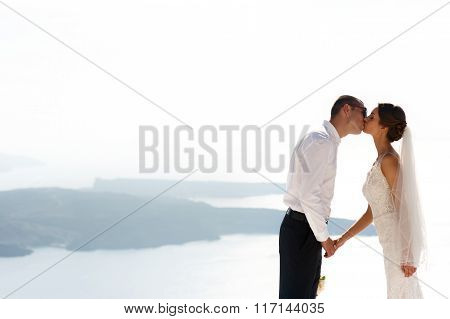 Handsome Happy Groom And Bride In White Dress Kissing Sea And Islands Background