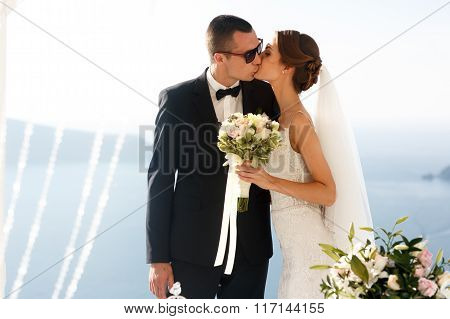 Happy Handsome Groom And Brunette Bride At Wedding Aisle With Sea In Background