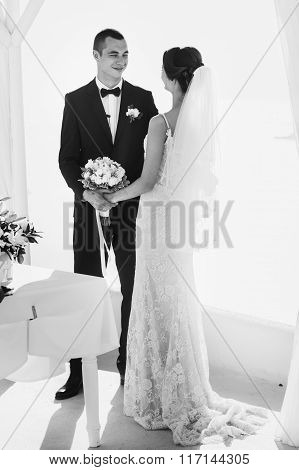 Happy Groom And Bride At Wedding Aisle During Ceremony With Sea In Background B&w