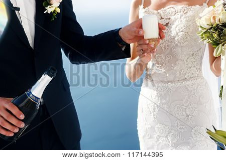 Groom And Bride Opening Champagne At Wedding Aisle Tent Sea Background Closeup
