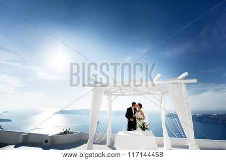Newlywed Couple Drinking Champagne In Glasses And Kissing Landscape Sea Background