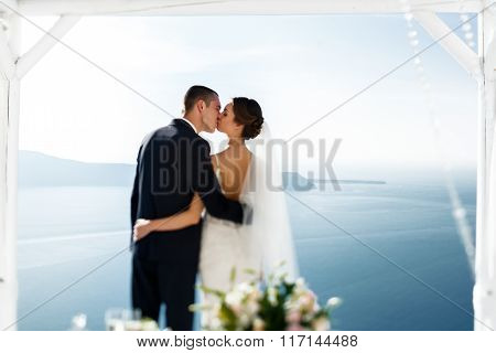 Newlywed Husband And Wife Kissing At Terrace Looking At Sea In Santorini