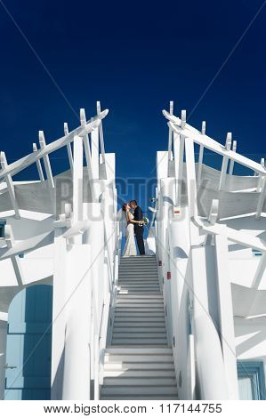Happy Romantic Bride And Groom Kissing On Top Of Stairs Modern Architecture And Sky