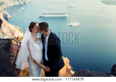 Bride And Groom Kissing At Sunset At Mountain Sea And Ships Background
