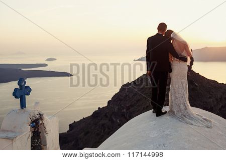 Handsome Groom And Beautiful Bride Hugging On Church Roof At Sunset Sky Background