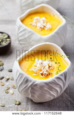 Pumpkin,corn soup with salty popcorn in a white ceramic bowl on a wooden background