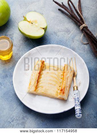 Apple tart, puff pastry strips with vanilla custard on a stone background