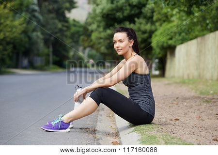 Young Female Athlete Sitting Outdoors Resting After Workout