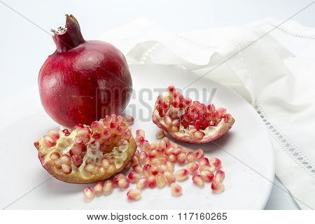 Pomegranate Whole And Pieces With Grains On A White Plate