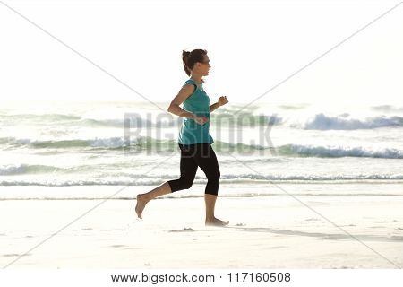 Portrait Of Young Woman Running Along The Beach
