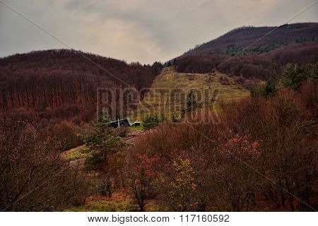 Autumn Landscape - Woods On The Hillsides. Ski Slope With Cableway In Fall. Mountain Village Podhrad
