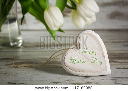 Wooden Heart Shape In Front Of White Tulips On A Gray Rustic Table For Mothers Day