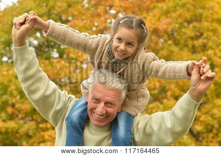 man with granddaughter in autumn park