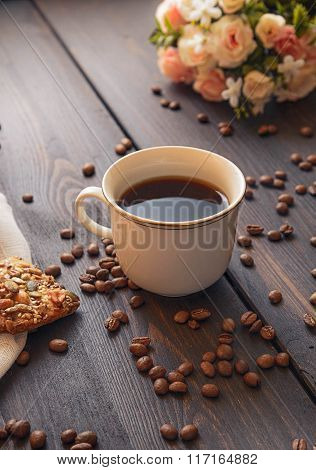 white cup of strong morning coffee on a brown table