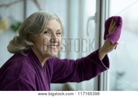Senior woman cleaning window