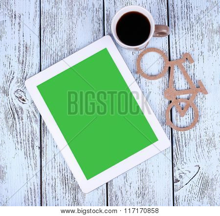 Tablet pc and mug of coffee on wooden background
