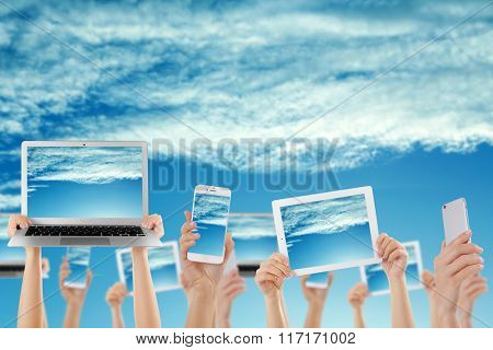 Hands holding electronic gadgets with sky on screens. Cloud computing concept