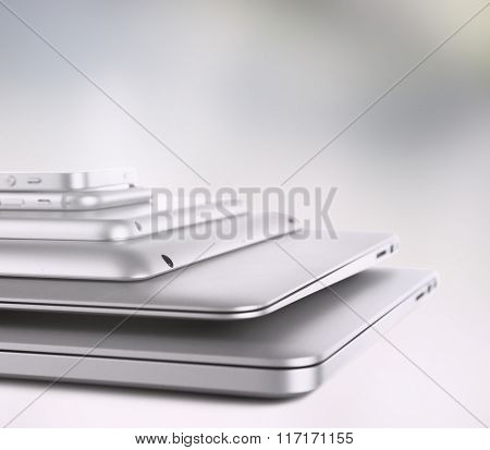 Pile of different modern electronics gadgets on abstract background