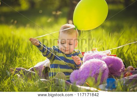 Little Baby Boy Playing Toys Sitting On Long Green Grass Outside In Backyard