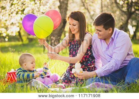 Dad And Mom Playing Games With Little Son Outside In Spring Blooming Garden