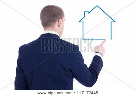 Real Estate Concept - Back View Of Young Business Man Drawing House Isolated On White