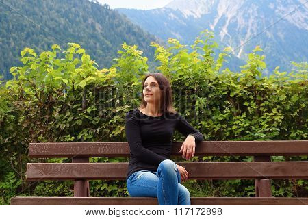Girl on the bench on the background of Alps