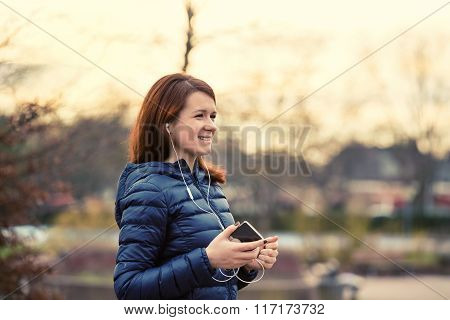 Happy young university student listening to music