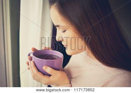 Woman drinking coffee in sunshine sitting near window in sun light enjoying her morning coffee.