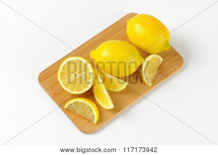 whole and sliced lemons on wooden cutting board
