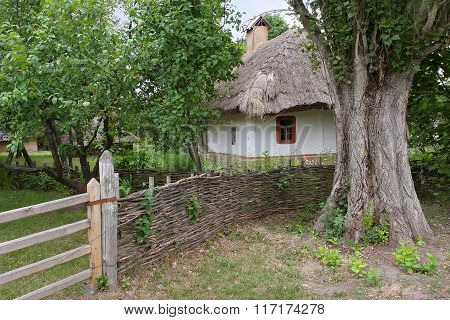 Old Adobe House Under A Thatched Roof With A Chimney Stove. Ecovillage Is Located In Eastern Europe.