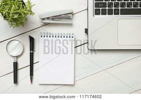 Office desk table with supplies. Top view. Copy space for text. Laptop, blank notepad, pen, magnifyi