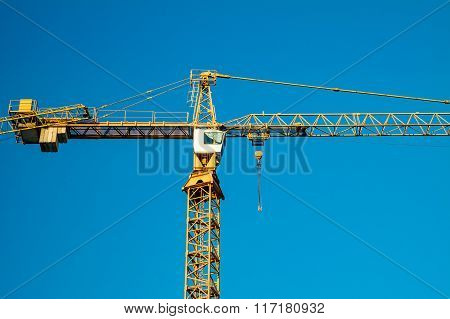 Building under construction and crane. Blue sky.