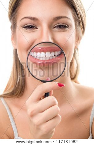Beautiful woman with magnifying glass showing her perfect white teeth