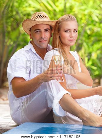 Loving couple sitting on the beach, drinking champagne on romantic tropical resort, spending happy summer holidays together