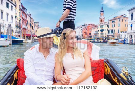 Young happy couple riding on a gondola on Grand Canal in Venice, spending honeymoon in Italy, Europe