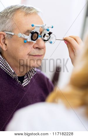 Ophthalmic doctor measure distance of eyes pupil in consulting room