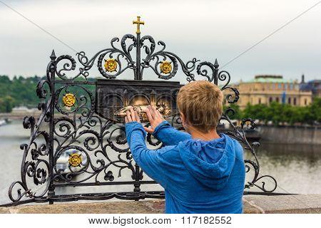 Tourist Touching The Sculpture Of Saint Jan Nepomuk On The Charles Bridge In Prague