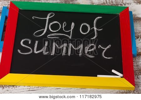 Blackboard with text it's Joy of summer on wooden deck